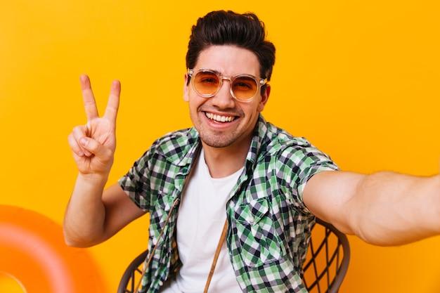 Actieve man in geruite outfit en bril vertoont vredesteken en maakt selfie op geïsoleerde ruimte.