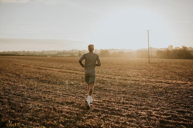 Actieve man in sportkleding die op het platteland loopt
