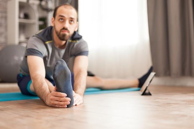 Actieve man op yogamat thuis die zijn lichaam uitrekt tijdens online les op tabletcomputer.