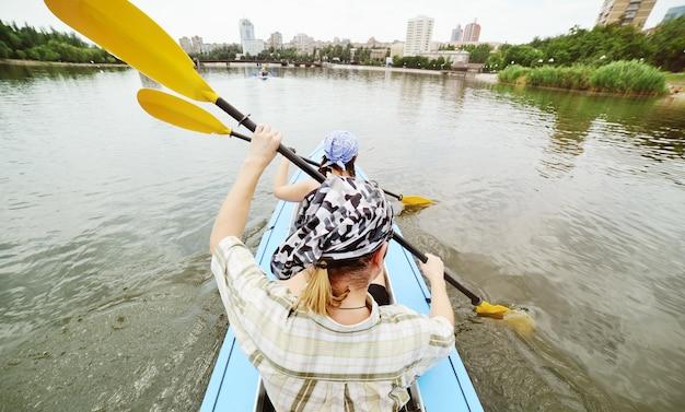 Actieve manier van leven - zwem in een kajak op de rivier tegen het oppervlak van de stad