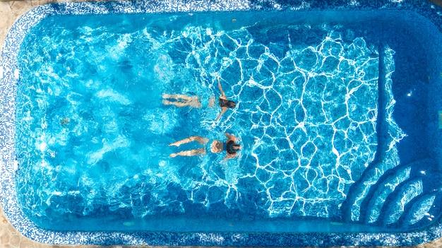 Actieve meisjes in luchtfoto van het zwembadwater luchtfoto van bovenaf, kinderen zwemmen, kinderen hebben plezier op tropische familievakantie, vakantieoord concept