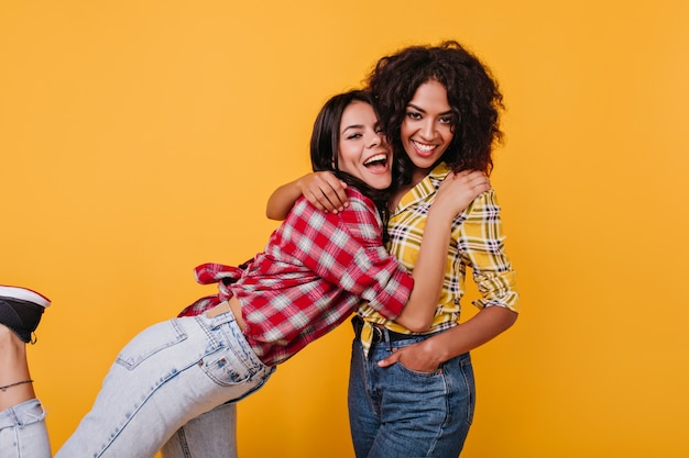 Actieve meisjes ontmoeten elkaar graag. brunette in rood overhemd koestert vriend met krullend haar.