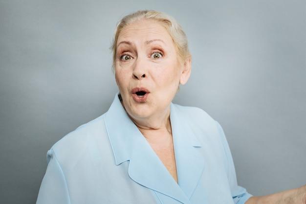 Actieve nabootsing. positieve vrouwelijke persoon die mond opent en camera bekijkt terwijl hij over grijze achtergrond staat