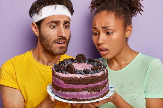 Actieve paar poseren met een grote taart