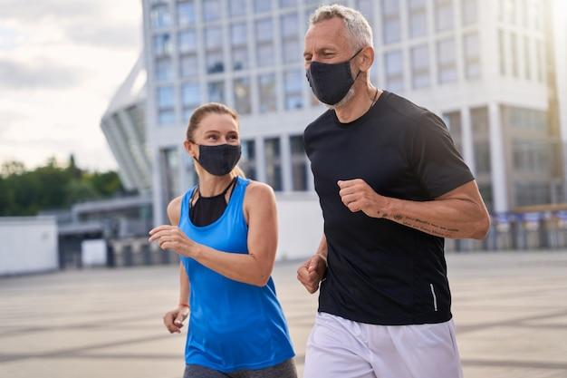 Actieve paar vrouw en man van middelbare leeftijd die beschermende maskers dragen terwijl ze buiten in de stad rennen