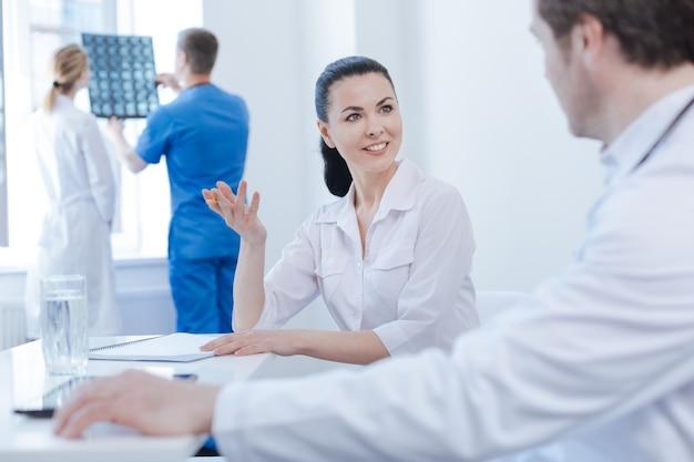 Actieve, prettige gekwalificeerde therapeuten die werken en meningen delen in het ziekenhuis terwijl ze digitale apparaten gebruiken en aantekeningen maken