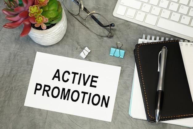 Actieve promotie - belettering op papier op het bureaublad, notitieblok, pen en toetsenbord. conceptfoto van het voordeel.