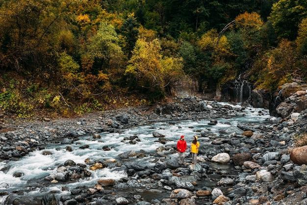 Actieve rust op de natuur. een paar toeristen die in de herfst langs een bergrivier lopen. een actief stel houdt zich bezig met wandelen. een jong stel houdt zich bezig met het volgen. ruimte kopiëren