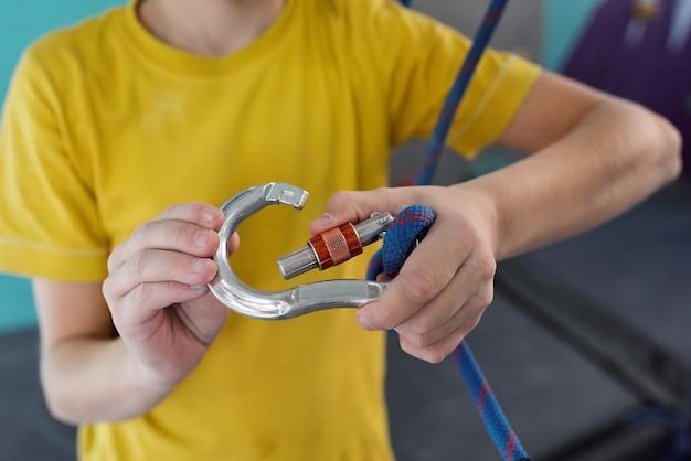 Actieve schooljongen vergrendelbare karabijnhaak met dik blauw touw terwijl hij zich op zijn gemak klaarmaakt om te klimmen