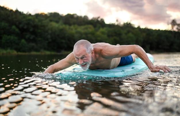 Actieve senior man op paddleboard op meer in de zomer, zwemmen.