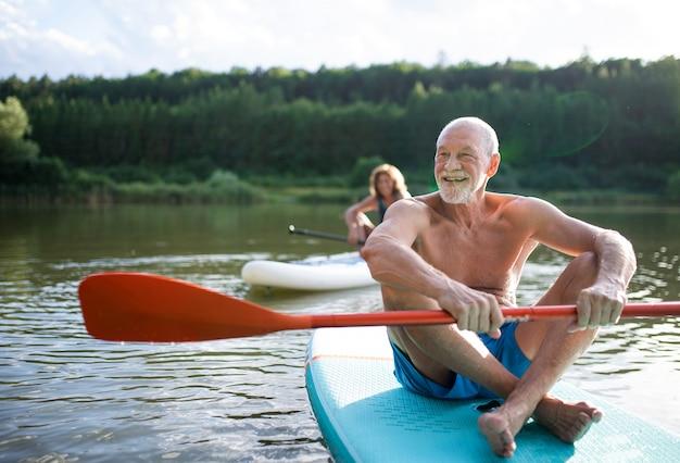 Actieve senior paar paddleboarding op meer in de zomer.