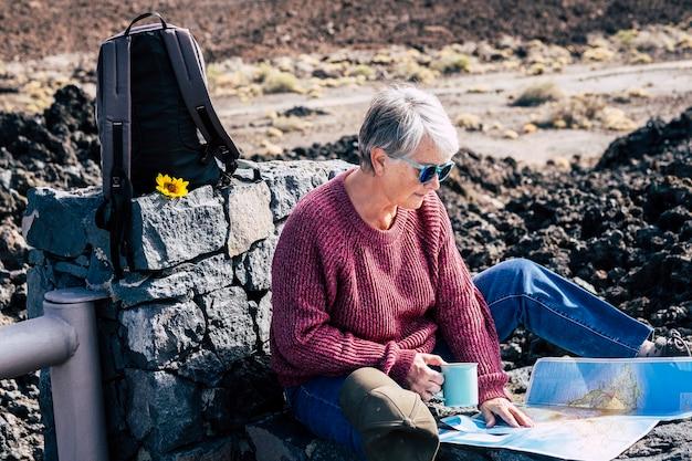 Actieve senior pensionering levensstijl met mooie volwassen blanke dame buiten zitten in reisrugzak alternatieve vakantie en vrijetijdsbesteding planning van de bestemming op een kaart