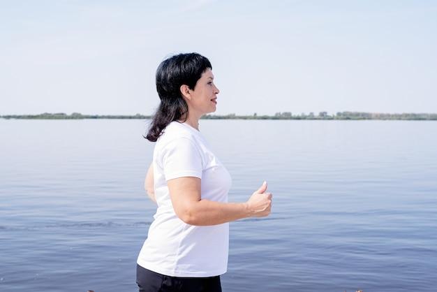 Actieve senior vrouw joggen in de buurt van de rivier