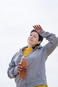 Actieve senioren. senior vrouw zweet wegvegen na een zware training buiten in het park