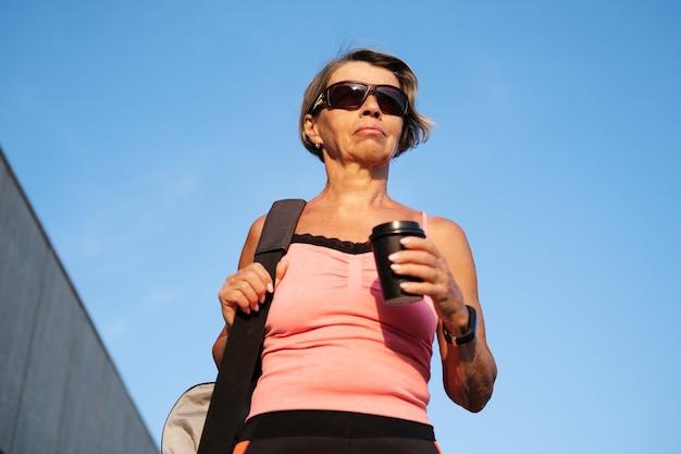 Actieve seniorenvrouw gaat op fitnesstraining in de stad met een kopje koffie, sporttas, slim horloge en zonnebril. sportieve fitness vrouw. gezonde levensstijl. hoge kwaliteit foto