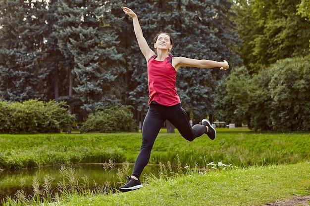 Actieve slanke jonge vrouw springt tijdens het maken van yoga in openbaar park in de buurt van vijver.