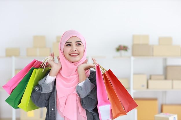 Actieve slimme aziatische moslimvrouw in het jasje die van jean zich en het winkelen zakken met online de leveringsachtergrond van de pakketdoos bevinden houden. mooi meisje dat camera en glimlach bekijkt. winkelen concept