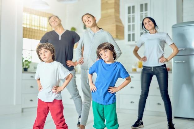 Actieve spaanse familie die 's ochtends samen thuis traint. familie, gezond levensstijlconcept. selectieve focus op tweelingen