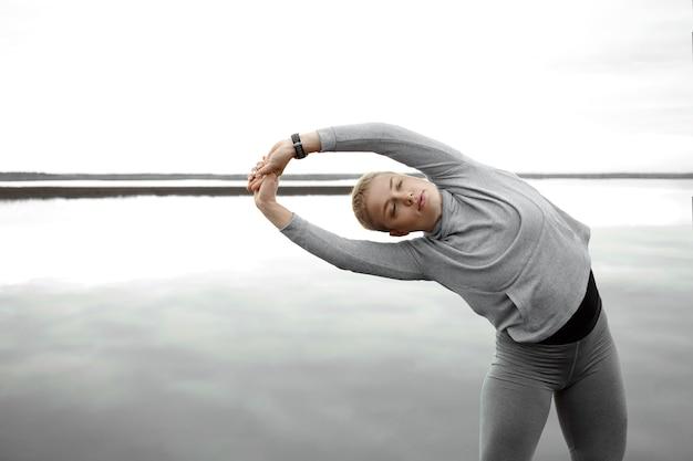 Actieve sportieve jonge vrouw in sportkleding die zijwaartse buighouding doet tijdens het beoefenen van ochtendyoga buiten bij rustige rivier. aantrekkelijke vrouw met kort blond haar en perfect fit lichaam armen strekken
