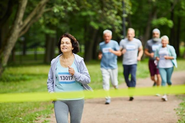 Actieve sportieve rijpe vrouw met bruin haar die deelnemen aan de marathonrace die het eerst afwerkt, kopie ruimte