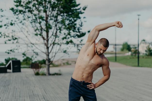 Actieve sportman die oefeningen buitenshuis doet