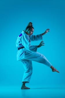Actieve training. professionele vrouwelijke judoist in witte judo kimono oefenen en trainen geïsoleerd op blauwe neoned studio achtergrond.