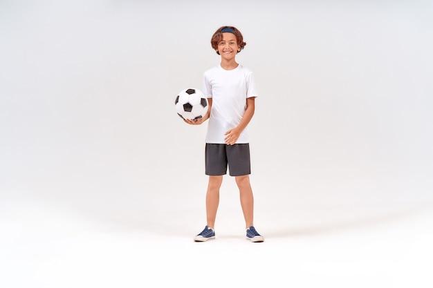 Actieve volledige opname van een gelukkige tiener met voetbal die naar de camera kijkt en glimlacht