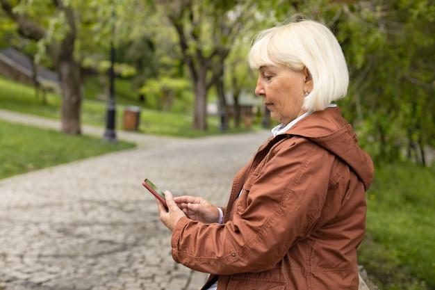 Actieve volwassen senior vrouw gebruikt smartphone terwijl ze op een bankje in het park zit