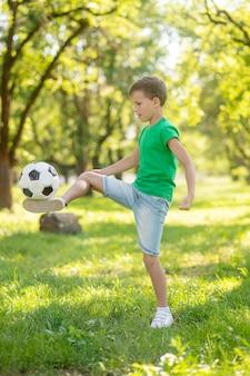Actieve vrije tijd. blonde geconcentreerde jongen in groene t-shirt en korte broek die voetbal op groen gazon vult