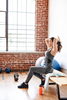 Actieve vrouw die haar haar bindt in de sportschool