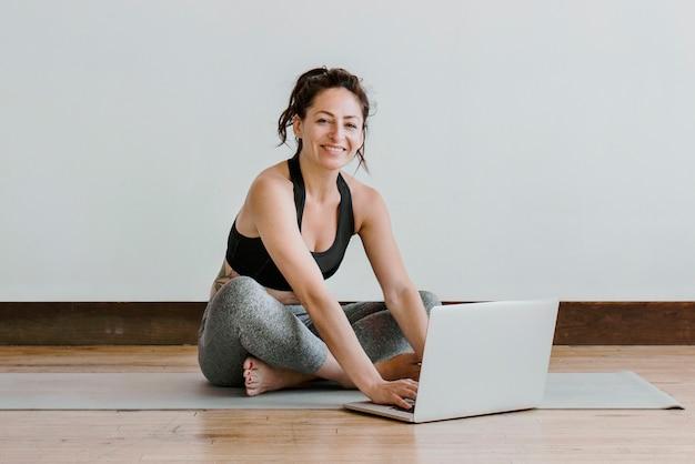Actieve vrouw die online yoga leert via een laptop