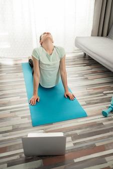Actieve vrouw die yoga thuis uitoefenen