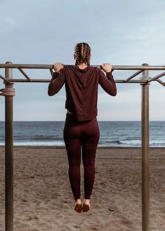 Actieve vrouw doet fitness oefeningen buiten aan het strand
