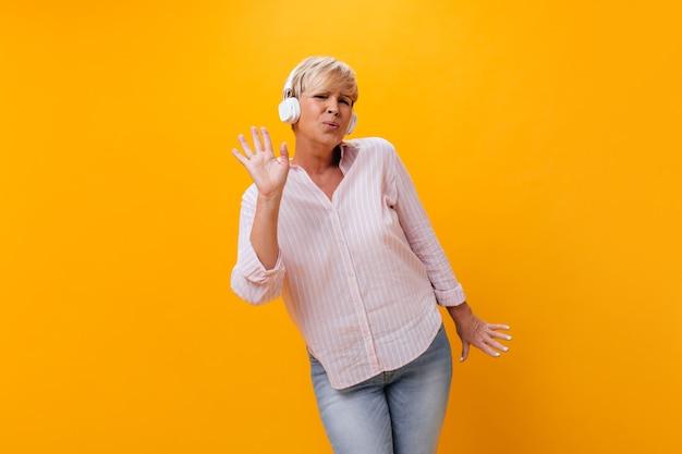 Actieve vrouw in hoofdtelefoons zingt en luistert naar muziek in hoofdtelefoons