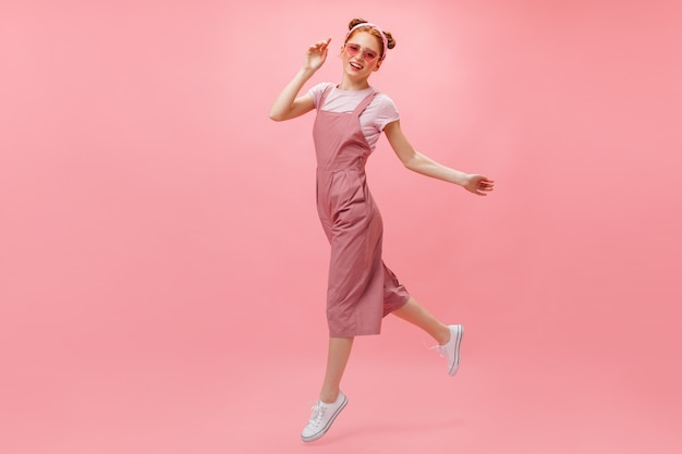 Actieve vrouw in roze jumpsuit, t-shirt en stijlvolle bril beweegt op roze achtergrond.