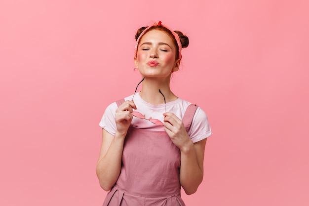Actieve vrouw in roze jurk en wit t-shirt luistert naar muziek in enorme koptelefoons.