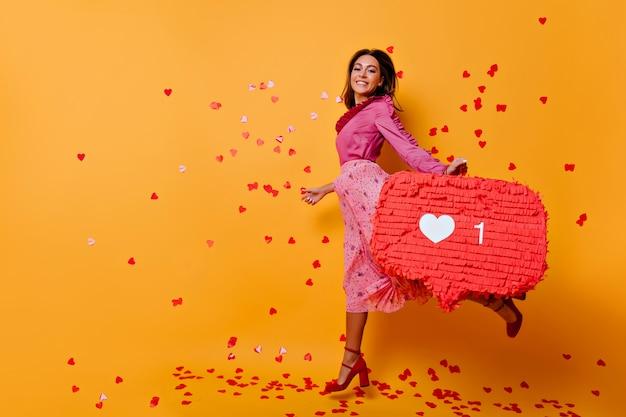 Actieve vrouw in roze kleren die pret hebben. emotioneel meisje dat met bruin haar op oranje muur springt.
