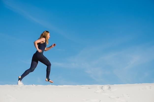 Actieve vrouw in sport slijtage joggen in de woestijn