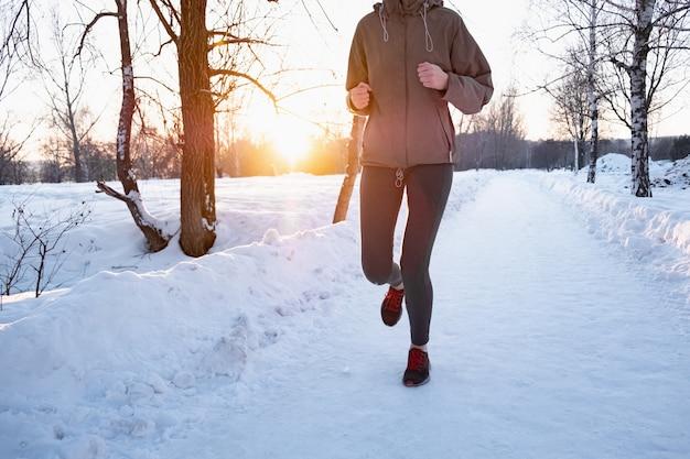 Actieve vrouw joggen buiten in de winter. vrouwelijke persoon die langs de sneeuwweg op mooie koude dag loopt