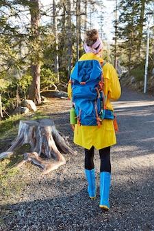 Actieve vrouwelijke ontdekkingsreiziger loopt door pad in bos, geniet van zonnige dag en mooi weer, draagt gele regenjas
