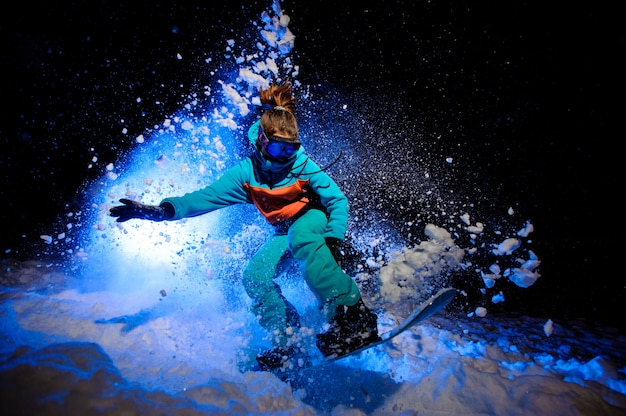 Actieve vrouwelijke snowboarder gekleed in een oranje en blauwe sportkleding die op de sneeuw springt