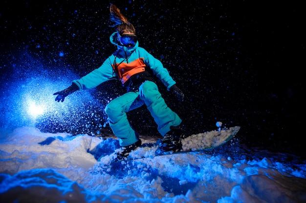 Actieve vrouwelijke snowboarder gekleed in een oranje en blauwe sportkleding springen op de berghelling