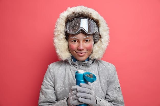 Actieve vrouwelijke snowboarder gekleed in warme bovenkleding heeft rode huid en bevroren gezicht tijdens koud winterweer drinkt warme drank uit thermoskan.
