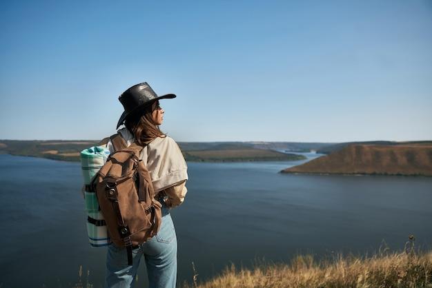 Actieve vrouwelijke wandelaar met rugzak die zich bovenop heuvel bevindt