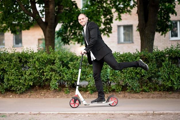 Actieve zakenman rijden scooter buitenshuis