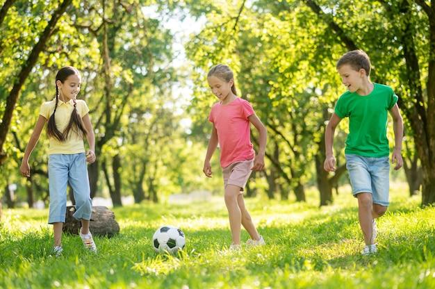 Actieve zomer. blonde jongen en twee langharige vrolijke vriendinnen voetballen op groen gazon op zonnige dag