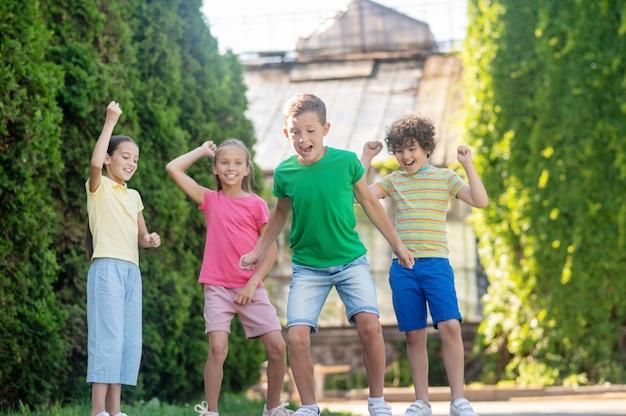 Actieve zomer. vrolijke jongen in groene t-shirt en korte broek met vrienden die actief spelen in het park op zonnige dag