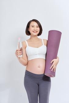 Actieve zwangere vrouw in sportkleding bedrijf uitoefenen mat en fles water, lege ruimte