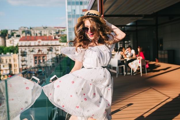 Activ meisje in zonnebril luistert naar muziek via een koptelefoon op het terras. ze draagt een witte jurk met blote schouders, rode lippenstift en hoed. ze danst als een gek.