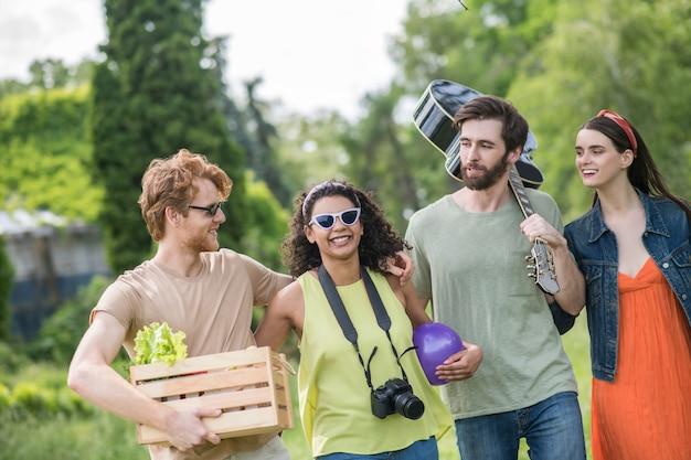 Activiteit, zomer. jonge vrolijke geknuffelde jongens met gitaar en eten en meisjes met camera en bal gaan picknicken in de natuur